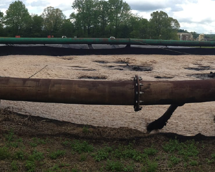 Raw Sludge Transfer Pipeline Cleaning Case Study. Image of raw sludge on an outdoor pipeline.